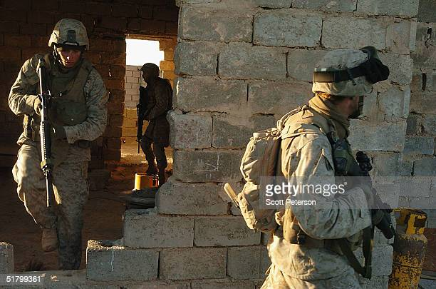 Lance Corporal Jason Bell steps through a wall as US Marines of the 1st Light Armored Reconnaissance company part of 1st Battalion 3rd Marines search...