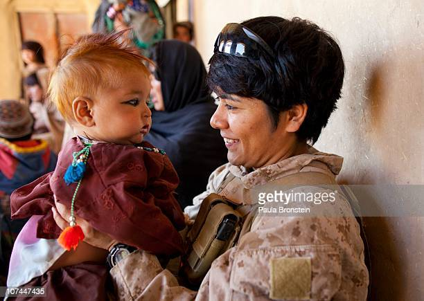 Lance Corporal Luz Lopez a US Marine with the FET 1st Battalion 8th Marines Regimental Combat team II plays with an Afghan baby girl during a village...