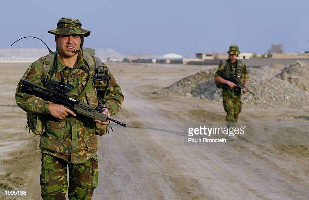 Lance Corporal Mark Schofield , a British International Security Assistance Force reserve soldier with the Lancastrian and Cumbrian Volunteers, walks...