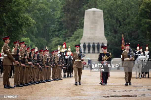 """Lance Corporal of Horse Carl Greenhow walks through an honour guard as he carries the Victorian-era replica of the """"Waterloo Eagle' as it is..."""