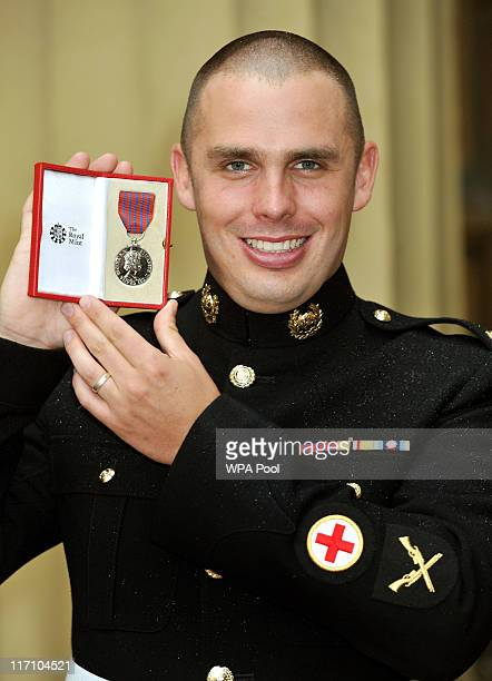 Lance Corporal Ryan Shelley of the Royal Marines holds his George Medal after it was presented to him by the Prince of Wales at the Investiture...