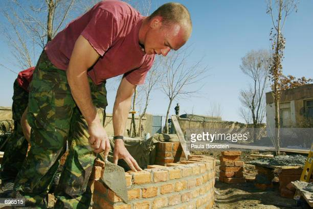 Lance Corporal Smudge Smith from Essex England a British Royal Engineer lays bricks while helping refurbish the Abdul Rahim Shaeed high school along...