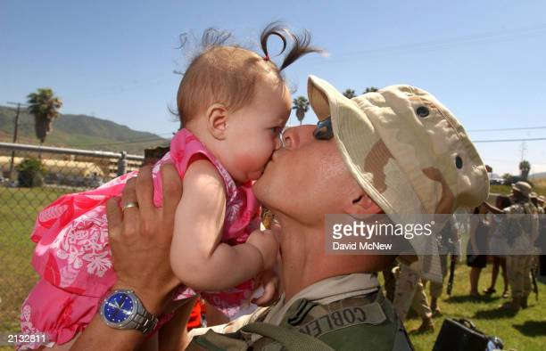 Lance Cpl Miguel Coblentz of 1st Battalion 11th Marine Regiment kisses 6monthold daughter Tiffany who was born just before he shipped out upon his...