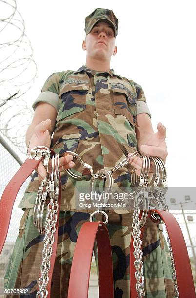 Lance Cpl Robert Devlin fr 2nd Military Police battalion 2nd Force Service Support Group displaying restraints used for transporting detainees to...