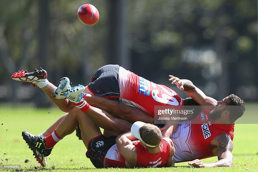 Lance Franklin (R) is tackled by teammates George Hewett and Ryan O'Keefe during a Sydney Swans AFL training session at Lakeside Oval on February 25, 2014 in Sydney, Australia.
