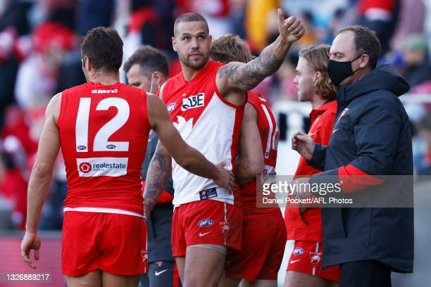 Lance Franklin of the Swans gestures to a friend in the crowd as Josh P. Kennedy of the Swans and Swans head coach John Longmire celebrate victory...