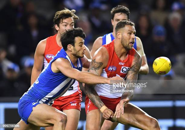 Lance Franklin of the Swans handballs whilst being tackled by Scott Thompson of the Kangaroos during the round 17 AFL match between the North...