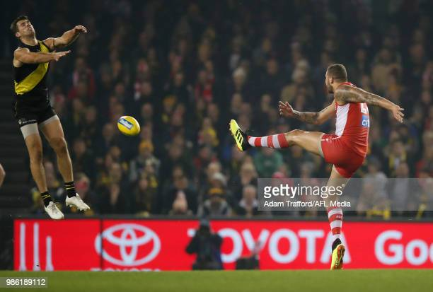 Lance Franklin of the Swans kicks the ball into Alex Rance of the Tigers and receives a 50m penalty for Rance stepping over the mark during the 2018...