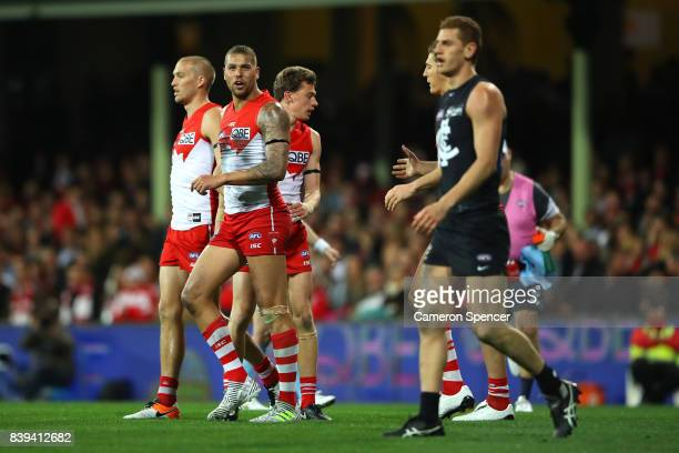 Lance Franklin of the Swans talks to Liam Jones of the Blues after kicking a goal during the round 23 AFL match between the Sydney Swans and the...