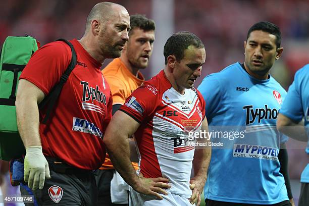 Lance Hohaia of St Helens is helped off the field by medics after being punched by Ben Flower of Wigan who was shown a red card during the First...
