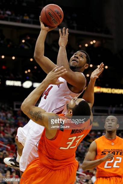 Lance Jeter of the Nebraska Cornhuskers goes up for a shot against Marshall Moses of the Oklahoma State Cowboys in the first half of their first...
