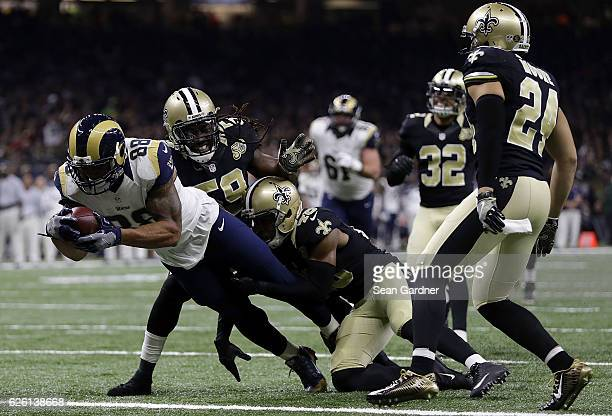 Lance Kendricks of the Los Angeles Rams scores a touchdown as Dannell Ellerbe of the New Orleans Saints and Vonn Bell defend during the first half of...