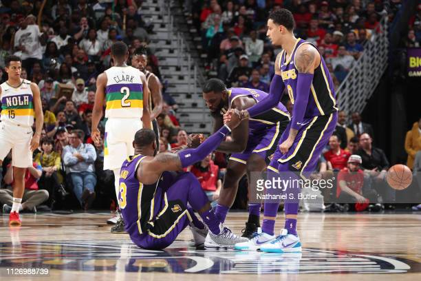 Lance Stephenson and Kyle Kuzma of the Los Angeles Lakers help LeBron James of the Los Angeles Lakers up during the game against the New Orleans...