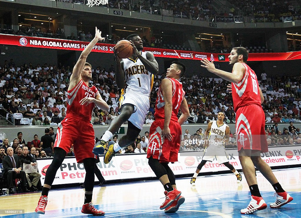 Lance Stephenson #1 of the Indiana Pacers passes ball over Chandler Parsons #25, Jeremy Lin #7 and Omri Canaan #18 of the Houston Rockets during the NBA match between the Houston Rockets and the Indiana Pacers at the Mall of Asia Arena on October 10, 2013 in Manila, Philippines.