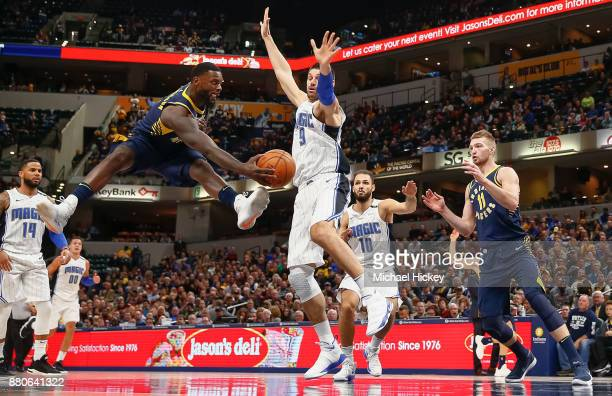 Lance Stephenson of the Indiana Pacers passes the ball off as Nikola Vucevic of the Orlando Magic defends at Bankers Life Fieldhouse on November 27...