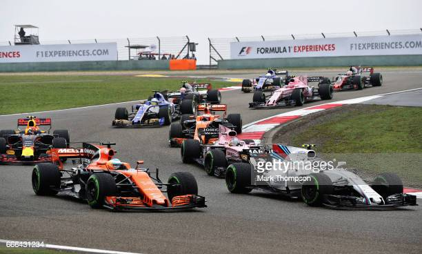 Lance Stroll of Canada driving the Williams Martini Racing Williams FW40 Mercedes battles with Fernando Alonso of Spain driving the McLaren Honda...
