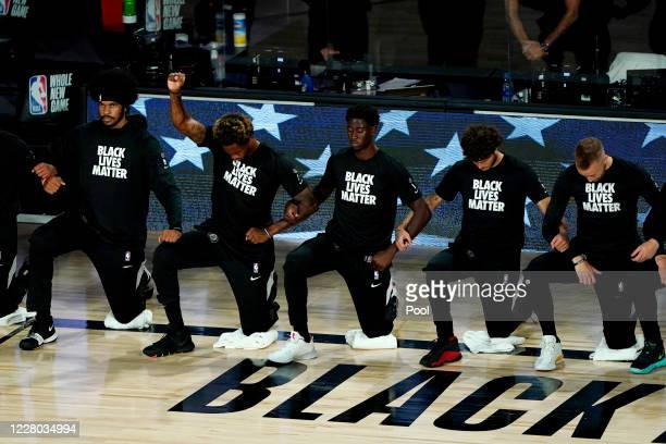 Lance Thomas of the Brooklyn Nets gestures as he and teammates kneel in honor of the Black Lives Matter movement prior to an NBA basketball game...