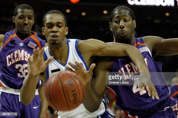 Lance Thomas of the Duke Blue Devils and James Mays of the Clemson Tigers along with Sam Perry of the Tigers go after a loose ball during the...