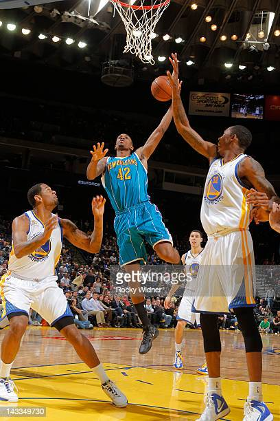 Lance Thomas of the New Orleans Hornets goes for a layup against Jeremy Tyler and Mickell Gladness of the Golden State Warriors on April 24, 2012 at...