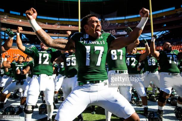 Lance Williams of the Hawaii Warriors leads his teammates in performing the 'haka' before the start of a college football game between the Washington...