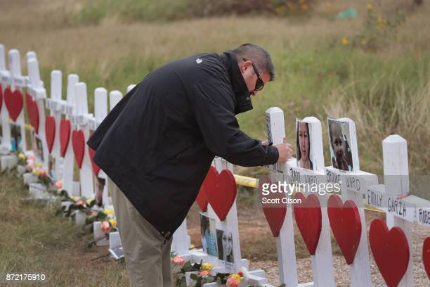 Lance Willis leaves a message at a memorial where 26 crosses were placed to honor the 26 victims killed at the First Baptist Church of Sutherland...
