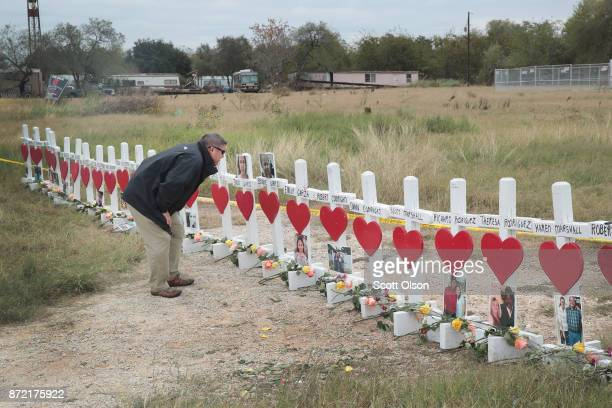 Lance Willis looks at pictures of victims at a memorial where 26 crosses were placed to honor the 26 people killed at the First Baptist Church of...