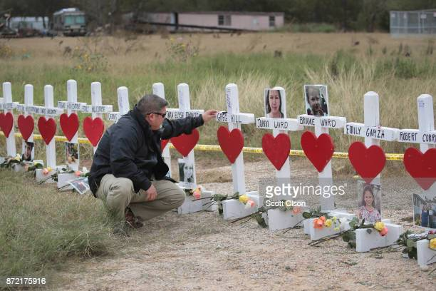 Lance Willis says a prayer at a memorial where 26 crosses were placed to honor the 26 victims killed at the First Baptist Church of Sutherland...