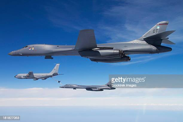 A B-1B Lancer stands by as another Lancer connects with a KC-135 Stratotanker.