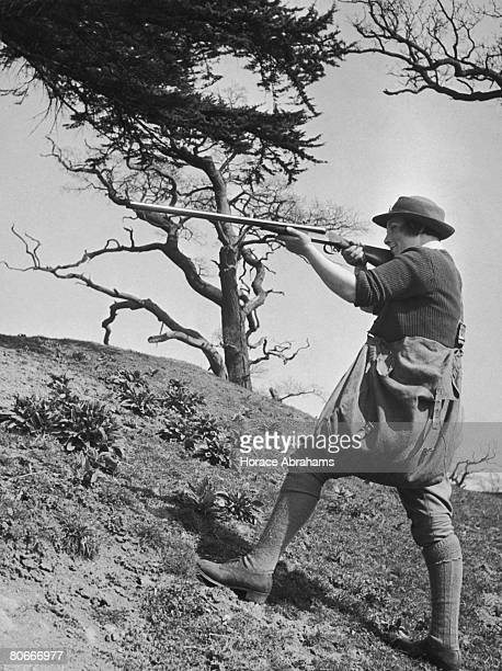 Land Army girl Doris Clements taking aim during a tour of a farm she is clearing of rabbits April 1942