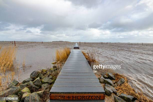 """land art pier and horizon wooden jetty on the shore of a lake with an approaching storm - """"sjoerd van der wal"""" or """"sjo"""" stock pictures, royalty-free photos & images"""