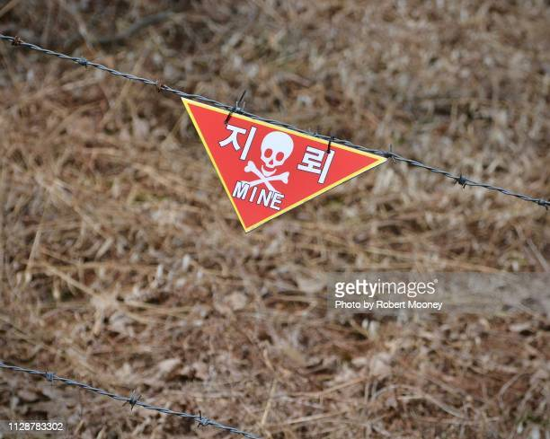 land mine warning sign and barbed wire in the korean demilitarized zone (dmz) - demilitarized zone stock pictures, royalty-free photos & images