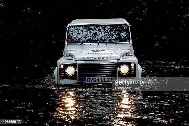 A Land Rover Defender automobile is driven around a live experience track at Tata Motors Ltd's Jaguar Land Rover vehicle manufacturing plant in...