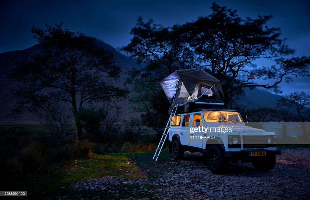 Land Rover Defender Camping With A Tent On The Roof Stock