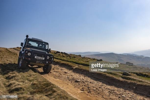 Land Rover Defender descends the track down Stanage Edge.