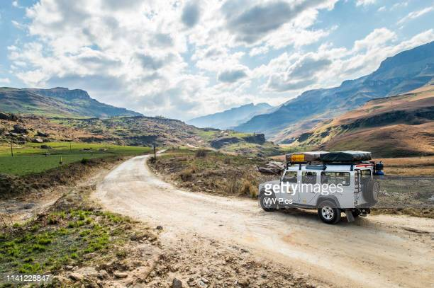 Land Rover Defender parked on a dirt road in Sani pass between South Africa and Lesotho.