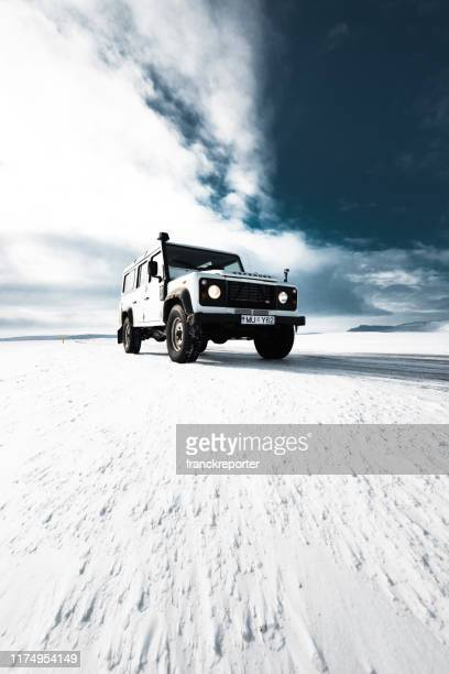 land rover defender parked on the road in iceland - monster truck stock pictures, royalty-free photos & images