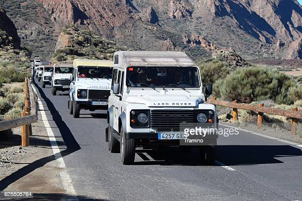 Land Rover Defender vehicles driving on the road