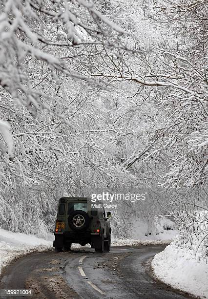 Land Rover drives beneath snow covered trees lining Cheddar Gorge near Cheddar on January 23, 2013 in Somerset, England. Parts of the UK, including...