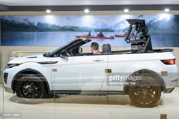 Land Rover Range Rover Evoque Convertible or just Range Rover Evoque Convertible compact SUV side view with a man sitting inside opening the roof on...