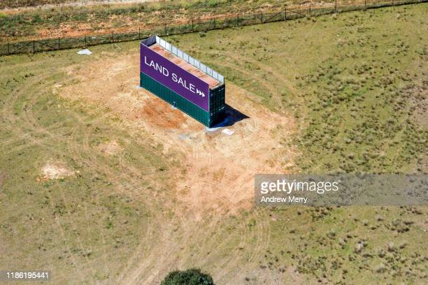 land sale sign, billboard by highway roadside at the edge of city, urban sprawl in sydney, australia, aerial photography - housing difficulties stock pictures, royalty-free photos & images