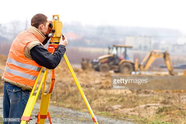 land surveyor on construction site - land stockfoto's en -beelden