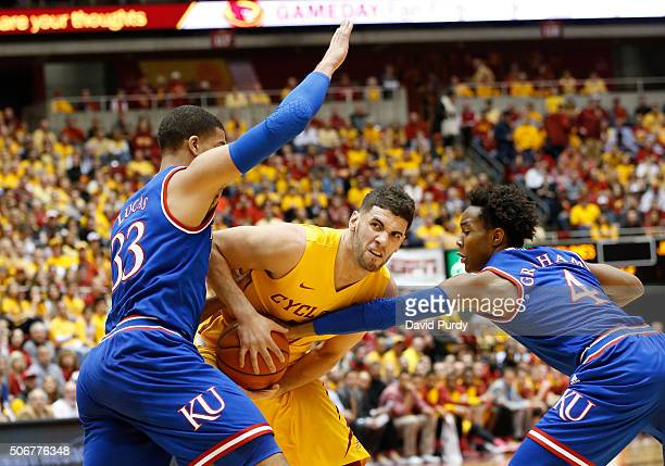 Landen Lucas and Devonte' Graham of the Kansas Jayhawks put pressure on Georges Niang of the Iowa State Cyclones as he drives the ball in the first...