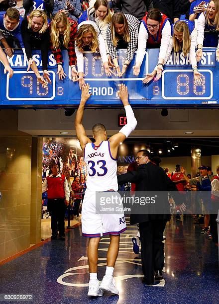 Landen Lucas of the Kansas Jayhawks highfives fans as he walks off the court after the Jayhawks defeated the Kansas State Wildcats 9088 to win the...