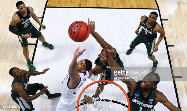 Landen Lucas of the Kansas Jayhawks jumps for the rebound against Joshua Langford of the Michigan State Spartans during the second round of the 2017...