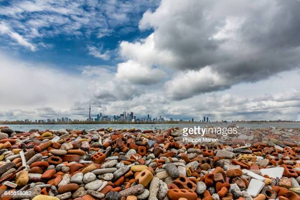 landfill debris of eroded and smashed bricks and large metropolis of toronto - lake ontario stock pictures, royalty-free photos & images