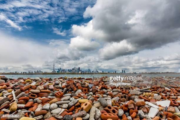 Landfill debris of eroded and smashed bricks and large metropolis of Toronto