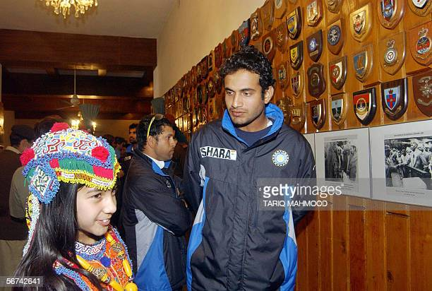 Indian cricketer Irfan Pathan looks at a traditionally dressed Pakistani girl while teammate Sachin Tendulkar looks at a display of plaques and...