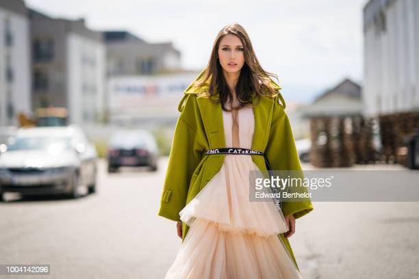 Landiana Cerciu Vice President of Feeric Fashion Week wears a green coat and a pink lace ruffled dress during Feeric Fashion Week 2018 on July 22...