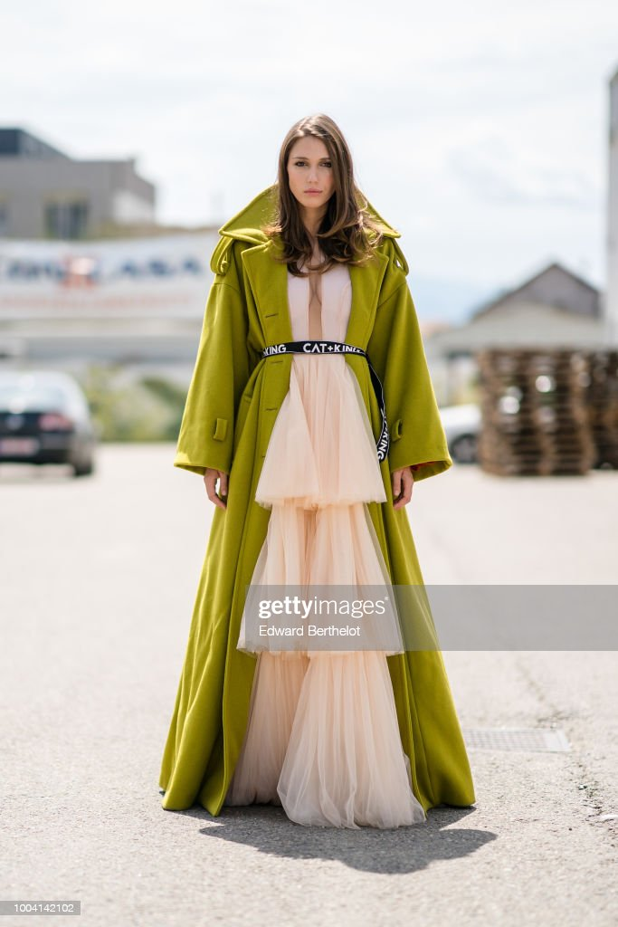 Landiana Cerciu, Vice President of Feeric Fashion Week, wears a green coat and a pink lace ruffled dress , during Feeric Fashion Week 2018, on July 22, 2018 in Sibiu, Romania.