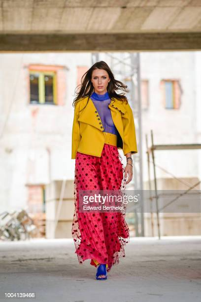 Landiana Cerciu Vice President of Feeric Fashion Week wears a yellow leather jacket a blue mesh cropped top top yellow pants a pink mesh skirt with...